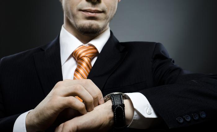 businessman in black costume wind clock (wristwatch) on hand,  close up